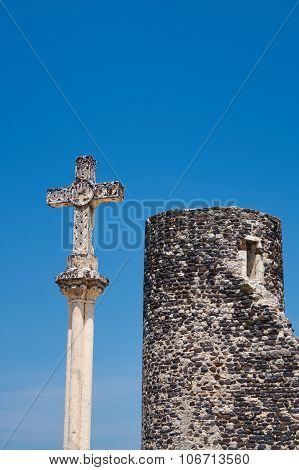 Stone cross and medieval tower in Saint-Vincent-de-Barres