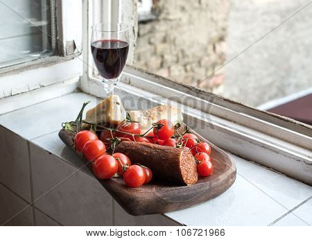 Home wine appetizer set. Glass of red wine, Hungarian spicy sausage, farmers cheese and cherry-tomat