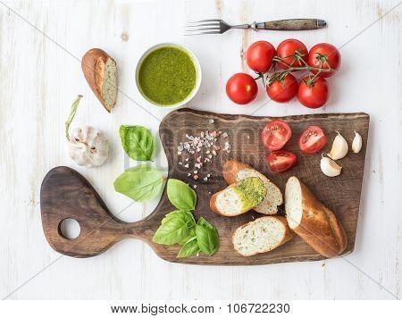 Pesto sauce, bread, cherry-tomatoes, fresh basil and garlic on rustic walnut chopping board over whi