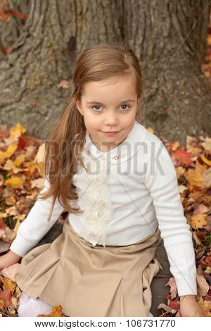 adorable little girl siting on a ground and smiling