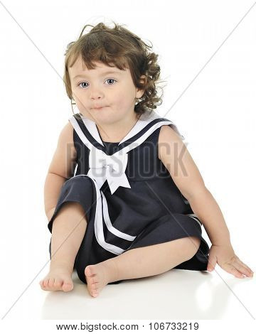An adorable toddler sitting barefoot in her sailor dress.  On a white background.