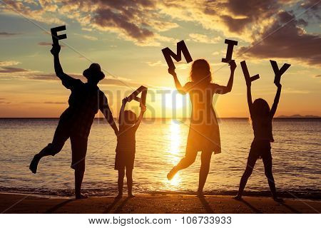 Happy Family Standing On The Beach At The Sunset Time.