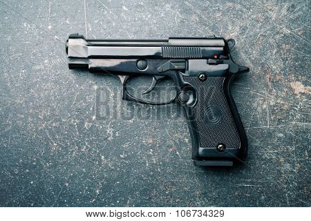 black handgun on old crackle background