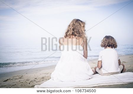 Mother And Son Sitting On The Beach At The Day Time.