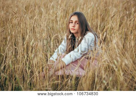 Young woman wearing dress sitting in field with wheat