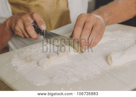 Hands cutting dough before cooking.