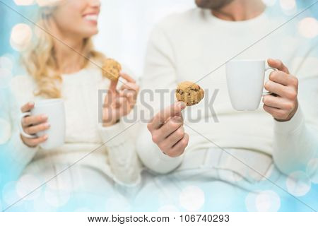 winter, love, food and sweets concept - close up of happy couple with oat cookies and tea cups at home over blue lights background