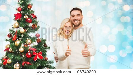 family, x-mas, winter holidays and people concept - happy couple showing thumbs up with christmas tree at home over blue lights background