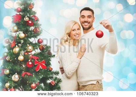 family, x-mas, winter holidays and people concept - happy couple decorating christmas tree with ball at home over blue lights background