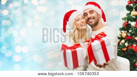 christmas, holidays and people concept - happy couple in santa hats with gift boxes sitting on sofa at home over blue lights background
