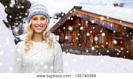winter, fashion, vacation, christmas and people concept - smiling young woman in hat and sweater over wooden country house and snowflakes background