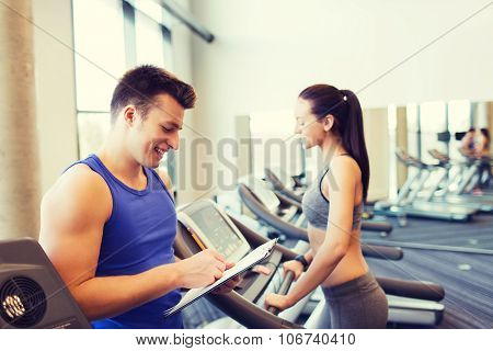 sport, fitness, lifestyle, technology and people concept - happy woman and trainer with clipboard working out on treadmill in gym