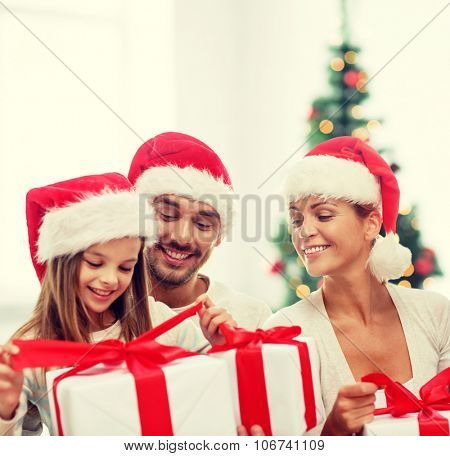 family, christmas, generation, holidays and people concept - happy family in santa helper hats with gift boxes sitting over living room with christmas tree background