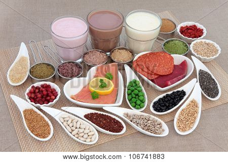 Health and body building high protein food of meat and fish, nuts, pulses, supplement powders, vegetables, fruit and smoothie juice drinks over bamboo and hessian background.