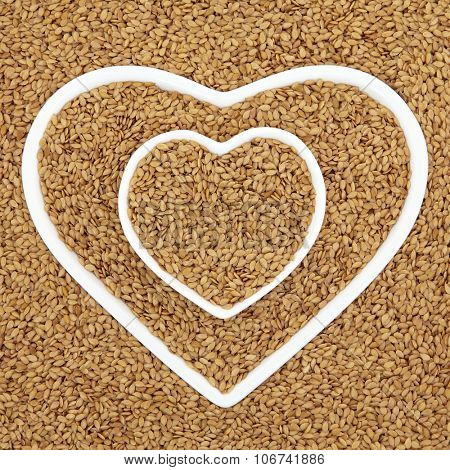 Golden flax seed health food in heart shaped porcelain bowls forming an abstract background.
