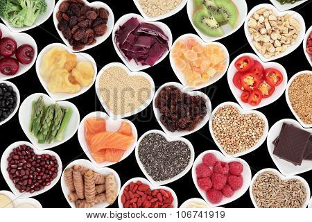 Healthy nutrition of superfood vegetable and fruit selection in heart shaped porcelain dishes over black background, high in vitamins and antioxidants.