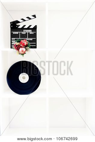 Movie Clapper Board, Film Reel And Christmas Decoration On Vertical White Bookshelf