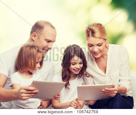 family, ecology, technology and people - smiling mother, father and little girls with tablet pc computers over green background
