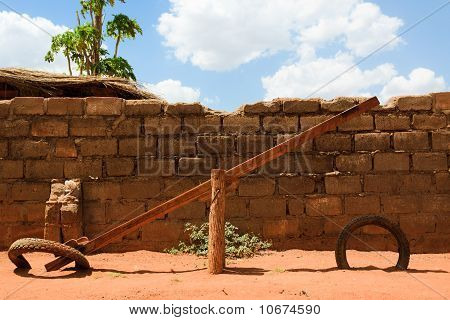 Seesaw On Red Sand Against Brick Wall