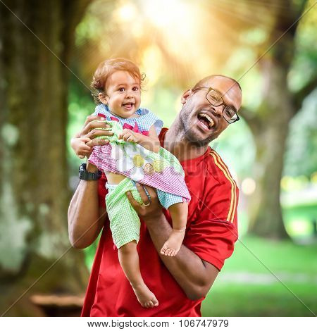 Father And Daughter Are Playing And Laughing In The Park.