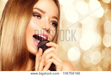 Singing Girl with microphone over golden glowing background. Karaoke party. Beauty model girl singer with a microphone singing and dancing. Disco party. Holiday Celebration
