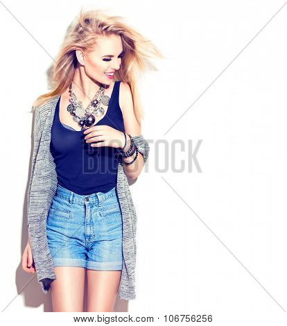 Fashion model girl portrait dressed in jeans shorts, long cardigan and modern accessories. Blowing hair. Street fashion, casual style. Isolated on white background