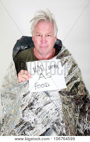A homeless man in a silver emergency survival space blanked with a will work for food sign.  In Black and White