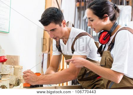 Carpenter team of woman and man working together