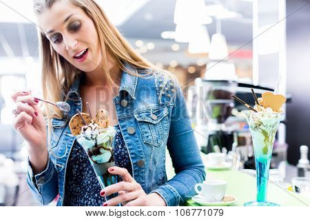Woman eating amaretto sundae in ice cream cafe