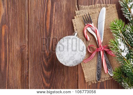 Christmas wooden background with silverware and snow tree