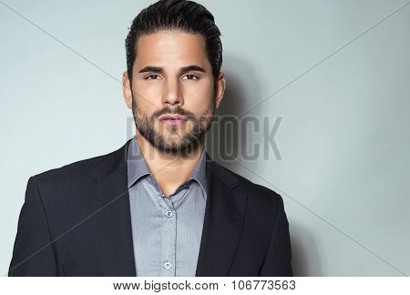 handsome young man in suit on grey background