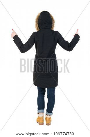 Back view woman  in parka thumbs up. Rear view people collection. backside view of person. Isolated over white background. Girl in a black winter jacket with a hood with two hands showing thumbs up.
