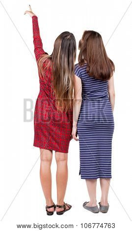 Back view of two pointing young girl. Rear view people collection.  backside view of person. beautiful woman friends  showing gesture. Rear view. I