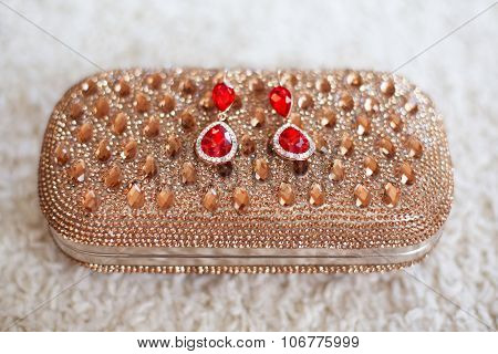Fashion Earrings With Red Rubies Jewels And Diamonds On Golden Purse With Strass And Gems.