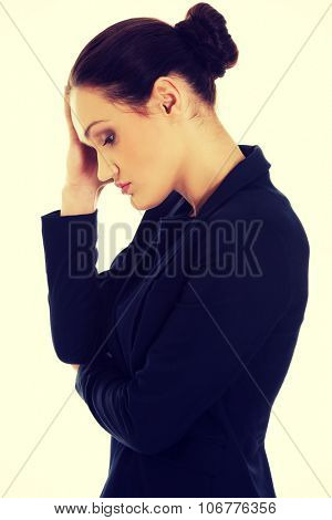 Worried businesswoman touching her head.