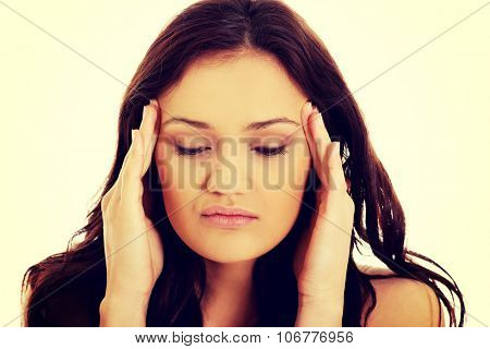 Young woman with a headache holding her head,.