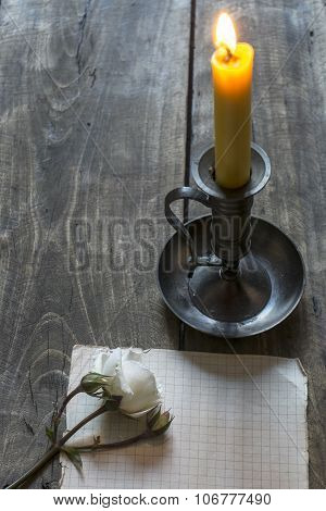 Old Sheet Of Paper, White Rose  And Candle On Wooden Background.