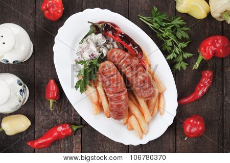 Grilled sausages with hot peppers and french fries, popular fast food meal