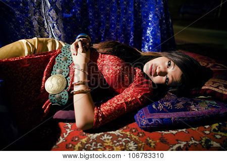 young pretty asian girl in bright colored interior on carpet vietnamese