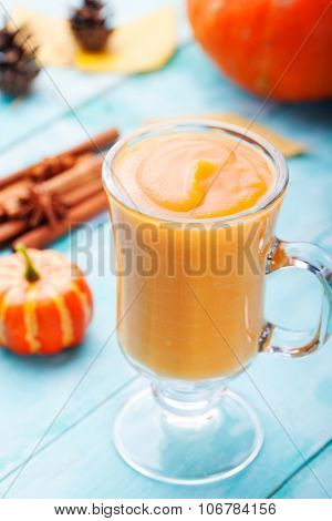 Pumpkin smoothie with pie spices on a turquoise wooden background