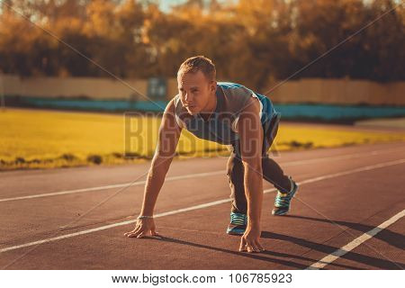 Athletic Man Standing In Posture Ready To Run On A Treadmill.