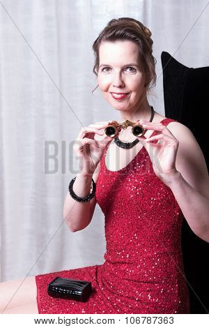 Attractive Woman In Red Dress With Magnifying Glass
