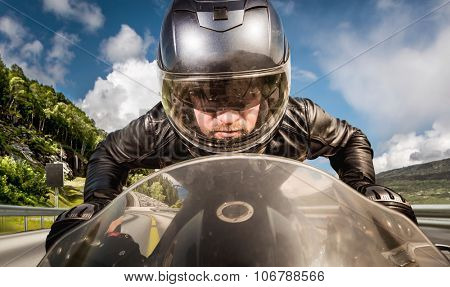 Biker in helmet and leather jacket racing on the road.