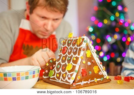Young Man Preparing A Gingerbread Cookie House