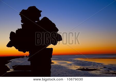 Silhouette of a mineral against sunrise on Chott El Jerid