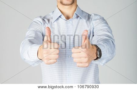 Young business man in white shirt gives thumbs up.