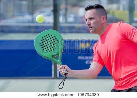 Man Playing Paddle Tennis Outdoors.