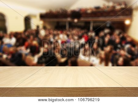 Blured big meeting of people and wooden desk on foreground