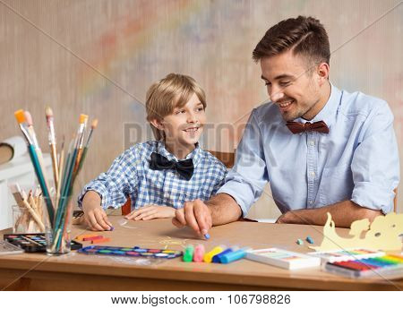 Boy And Dad Painting Together