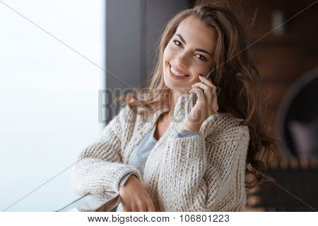 Portrait of a happy woman talking on the phone in apartaments